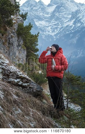 Relaxing mountaineer drinking hot drink from steel vacuum flask at snowy winter mountains background