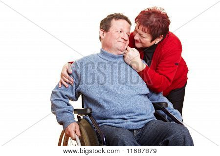 Senior Woman Caring For Man In Wheelchair