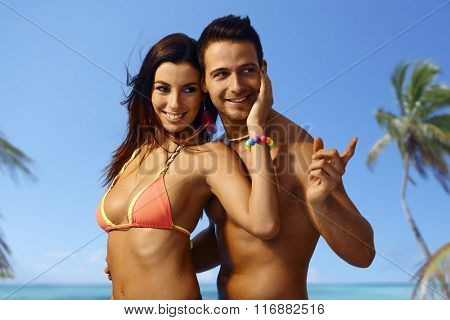 Attractive young loving couple embracing on the beach at summer holiday, smiling.