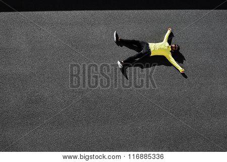 Top View Runner In Yellow Sportswear Resting Lying On A Black Asphalt After Running. Jogging Man Tak