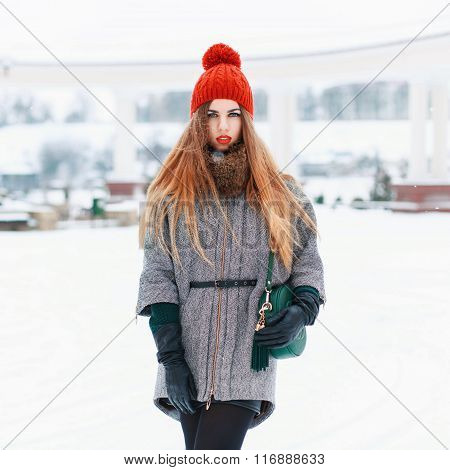Beautiful Woman In A Red Knit Hat And Winter Coat On A Winter Background
