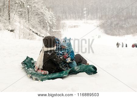 Young Children And Toddler Start A Downhill Ice Slide
