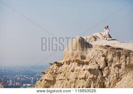 man and woman standing on the rock beach poster