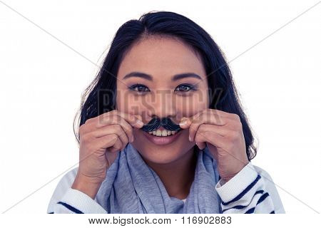 Pretty Asian woman with fake mustache posing for camera on white screen