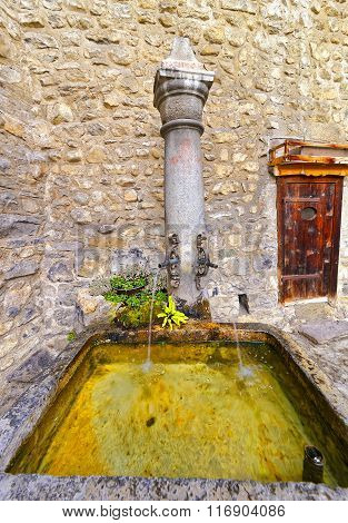 VEYTAUX SWITZERLAND - JANUARY 2 2015: Fountain with drinking water in Inner Court of Chillon Castle. It is an island castle on Lake Geneva (Lac Leman) in the Vaud between Montreux and Villeneuve.