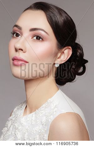 Portrait of young beautiful dreamy bride with stylish make-up and prom hairdo