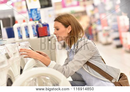 Woman in supermarket comparing washing machine details with smartphone
