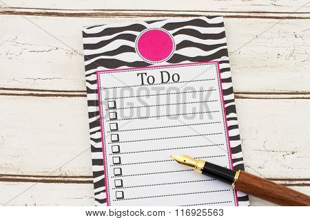 A Notepad And Pen On Weathered Wood Background With Text To Do And Copy-space