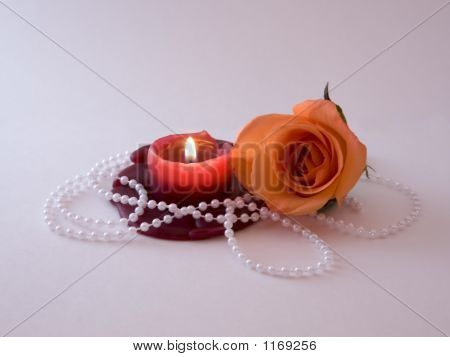 an orange rose bloom resting beside a lit candle with a bead faux pearl necklace entwined. poster