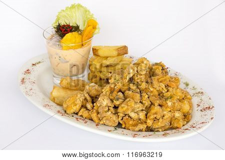 Peruvian food: chicharrones de pescado, a fried fish dressed with onions and pepper, and a chop.