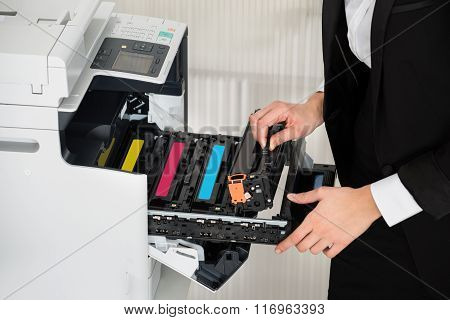 Midsection of young businesswoman fixing cartridge in printer machine at office poster
