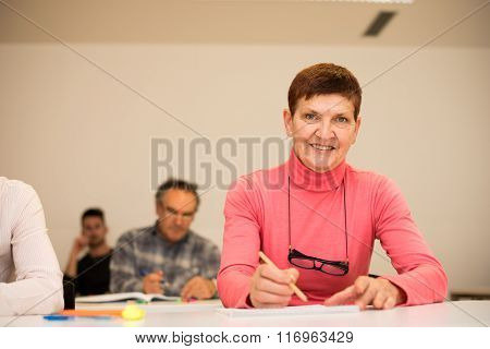 Group Of People Of Different Age Sitting In Classroom And Attending A School For Adults. Lifelong Le