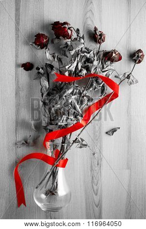 Bouquet of red roses with red ribbon in a glass vase thrown on the wooden floor.