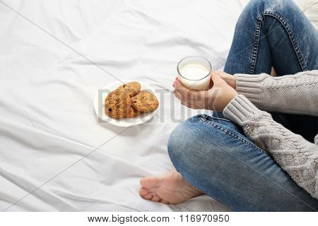 Woman drinking milk with cookies on her bed