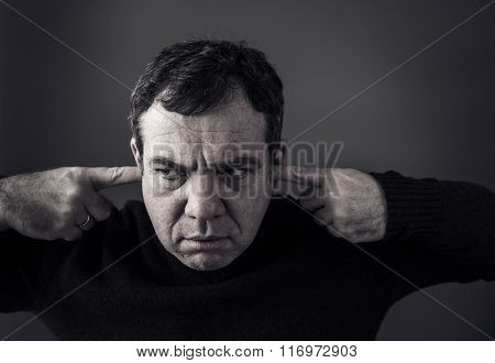 Headshot displeased man plugging ears with fingers doesn't want to listen. Black and white photo