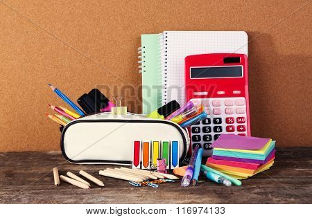 Pencil case with various stationery on old  wooden table poster