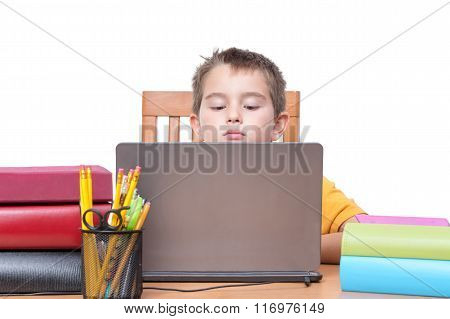Young Boy On Laptop Studying At Desk With Books