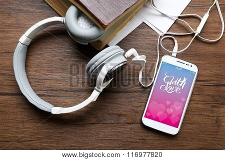 Headphones with old book and smartphone with romantic screensaver