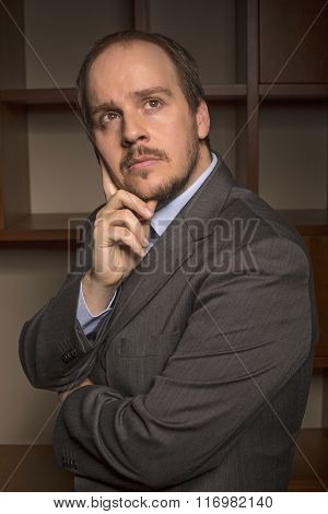 business man in home office with thoughtful look