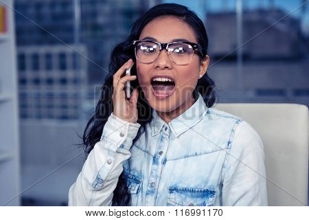 Asian woman shouting on phone call in office