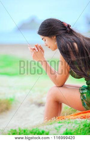 Beautiful Biracial Teen Girl Sitting At Tropical Beach, Praying