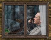 Rain, the window of the apartment. Outside, the profile of a man with a cat in her arms. The man smokes a cigarette, the smoke is visible. On the windowsill houseplant. Portrait of a man outside the window poster