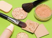 Makeup products to even out skin tone and complexion: concealer correcting powder liquid foundation its open bottle jar of loose powder crushed compact powder makeup brushes cosmetic sponge poster