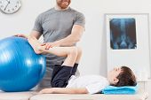Young kid undergoing physiotherapy with fitness ball poster