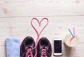 Sport concept healthy lifestyle. Female sportshoes towel cell phone and smoothie in the cup on the floor ready for jogging. Top view poster