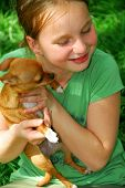 smiling young girl holding a chihuahua puppy (who just licked her:)) poster