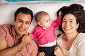 High angle view of a couple of attractive young Hispanic parents lying in a bed with their cute baby girl poster