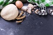 Dough and ingredients for it - eggs flour yeast on dark slate background. Selective focus. Place for text. poster