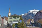 Catholic Church and Mountain in Bad Ragaz. Bad Ragaz is a city in canton St. Gallen in Switzerland. It lies over Graubunden Alps. Spa and recreation village is at end of Tamina valley poster
