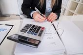Close-up Of A Businesswoman Calculating Invoice With Calculator poster