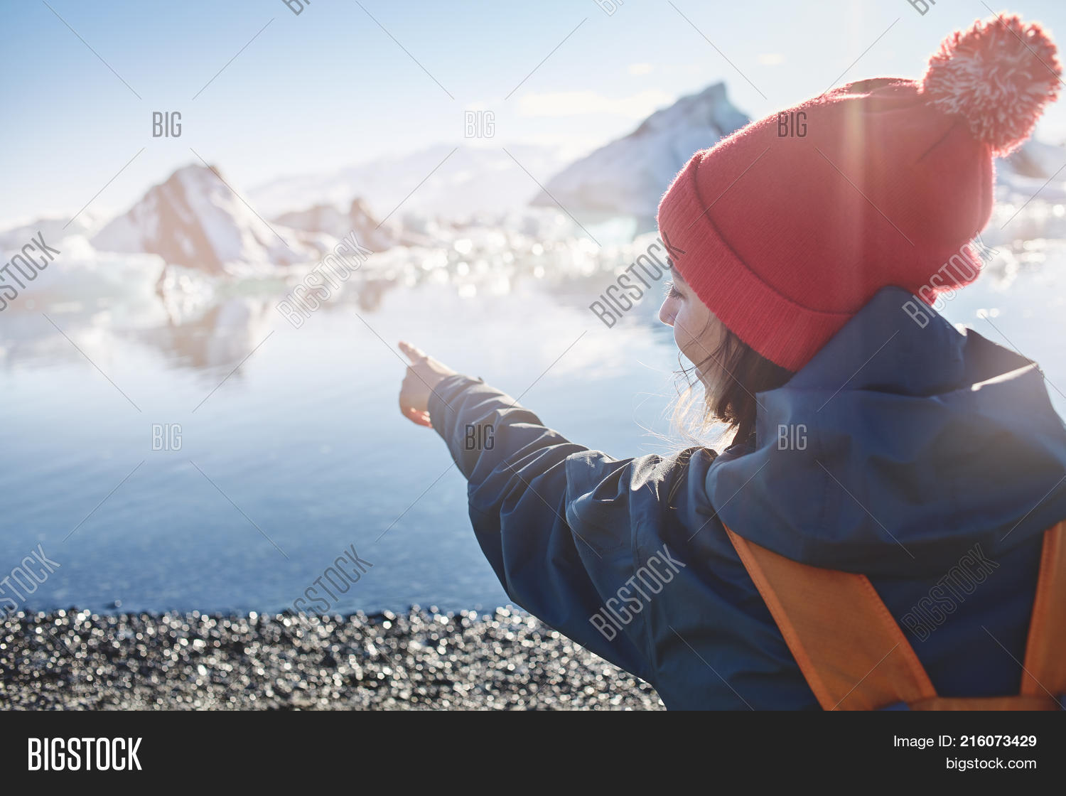 8e4d48ab2a1 back view of woman in warm clothing and knitted red hat with orange  backpack in Ice