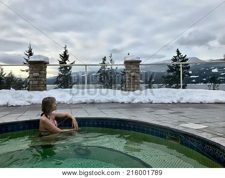 Woman in Hot Springs Pool with hot mineral healing water. Winter season in Canadian Rockies. Hot mineral pool surrounded with mountains trees and snow. British Columbia. Canada.