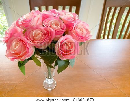 luxury pink rose on the wooden din table