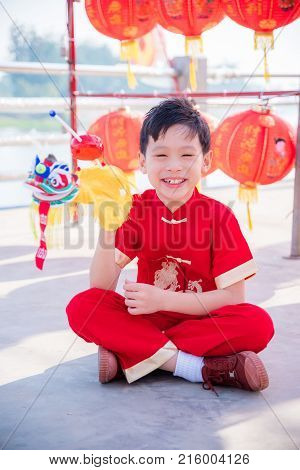 Young chinese boy wearing traditional dreass and playing lion puppet in chinese new year festival