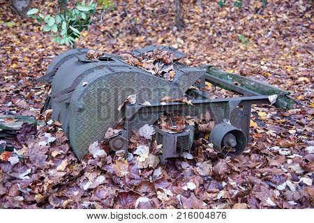 Rusty old machine laying in leaves on ground