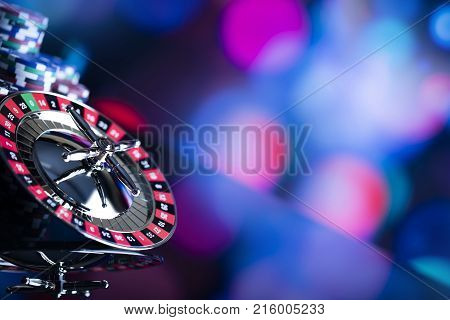 Casino theme. High contrast image of casino roulette and poker chips on a gaming table, all on colorful bokeh background. Place for typography and logo.