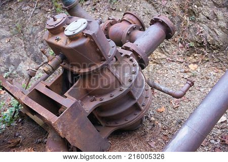 Rusty old machine part laying on ground