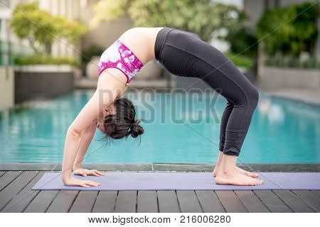 Beautiful young Asian woman doing yoga exercise with Chakrasana posing (the wheel pose) near swimming pool. Healthy lifestyle and good wellness concepts