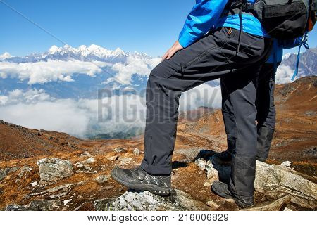 Couple's tourists legs together on top of the hill with mountain ridge on the background the mountains. Success freedom and happiness hike in the mountains for a vacation. Active sport concept.