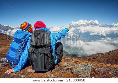 Two Hikers with Backpacks sitting on top of mountain discussing the Rout and pointing in high Mountains peak of Himalaya range. Travel sport lifestyle concept