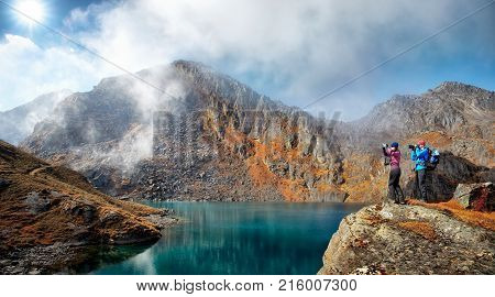 Couple tourists with backpacks take pictures to the background of beautiful blue lake and mountains during a hike. Young people in a mountain hike in Himalayas. Freedom and travel concept.