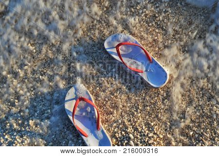 Summer vacation concept--Flip-flops on beach/ flip-flops in the sea