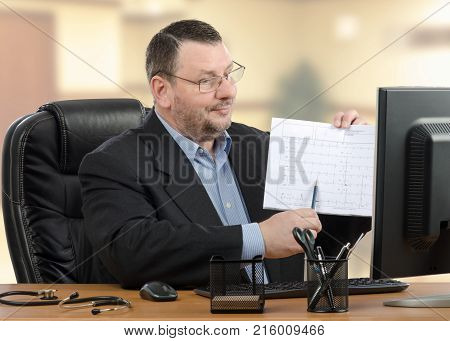 Accomplished doctor explains results of a medical outcomes to someone during telemedicine conference. Man in black suit shows printed sheet to monitor sitting at wooden office desk. Indoors blurred background