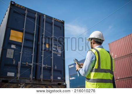 Foreman control loading Containers box from Cargo freight ship for import export foreman control Industrial Container Cargo freight ship.