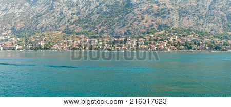 Panorama of Kotor Bay with a fragment of the ancient city of Kotor, Montenegro. View of the Balkan mountains from the waters of the Adriatic Sea.