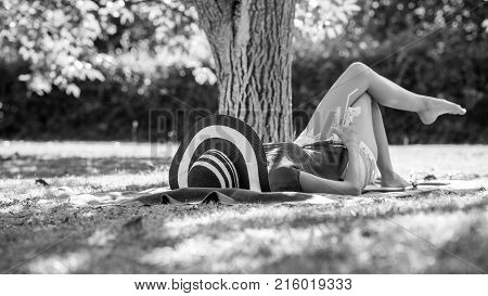 Monochrome Image Of A Woman Relaxing Outdoors In The Garden In Her Sunhat